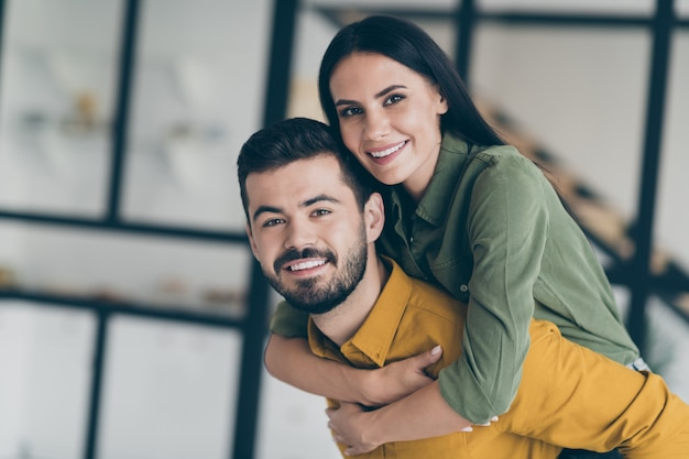 Closeup   handsome husband guy and his wife lady excited to start honeymoon in modern luxury country house flat holding piggyback