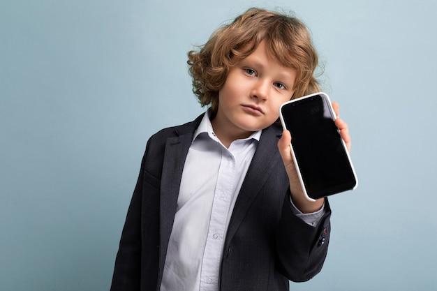 Крупным планом красивый серьезный спокойный ребенок мужского пола с вьющимися волосами в костюме, держащем телефон