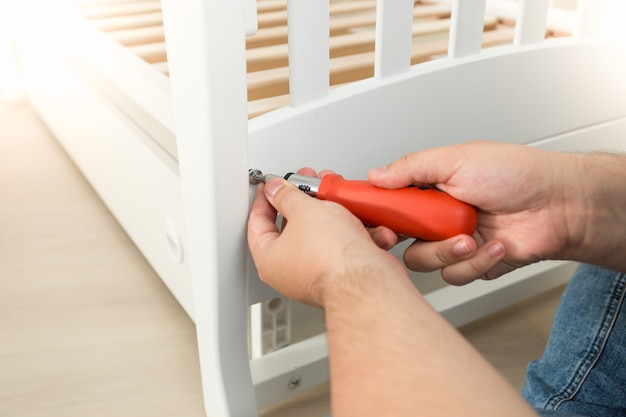 Closeup of handyman tightening the screws on white wooden bed