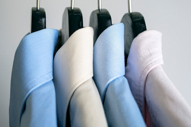 Closeup of hangers with business shirts row of colored shirts on a rack
