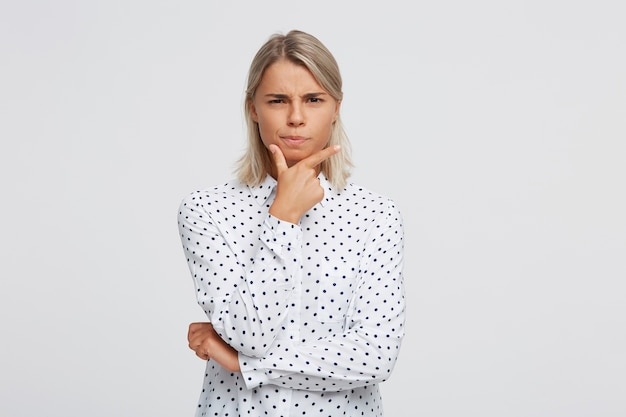 Closeup of happy amazed blonde young woman with opened mouth wears polka dot shirt feels surprised and points to the side with finger isolated over white wall