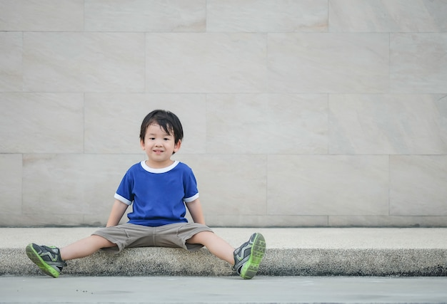 Closeup happy asian kid with smile face sit at pathway on marble stone wall textured background with copy space