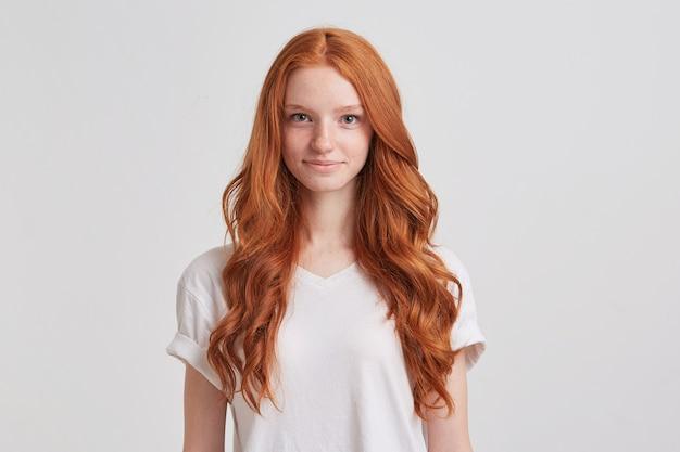 Primo piano di felice attraente giovane donna con lunghi capelli rossi ondulati