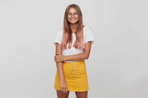 Primo piano di felice bella giovane studentessa con capelli rosa pastello tinti lunghi indossa maglietta, gonna gialla e occhiali in piedi, sembra allegro e posa isolato sopra il muro bianco