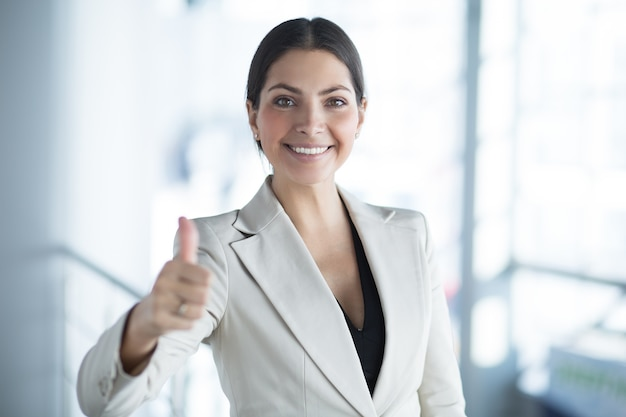 Closeup of happy business lady showing thumb up
