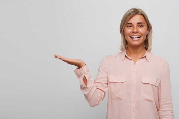 Closeup of happy confident blonde young woman with braces on teeth wears pink shirt smiling and holding copyspace on palm isolated over white wall