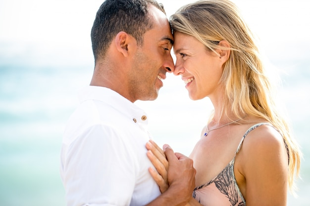 Closeup of happy couple touching foreheads by sea