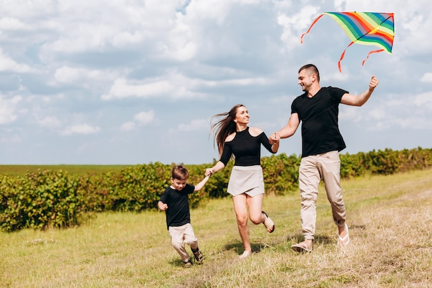 Closeup happy family  launch a kite on nature.