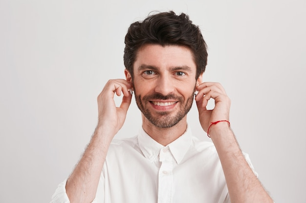 Closeup of happy handsome young businessman with bristle and wireless earphones wears shirt looks confident, smiling and listening to music isolated on white