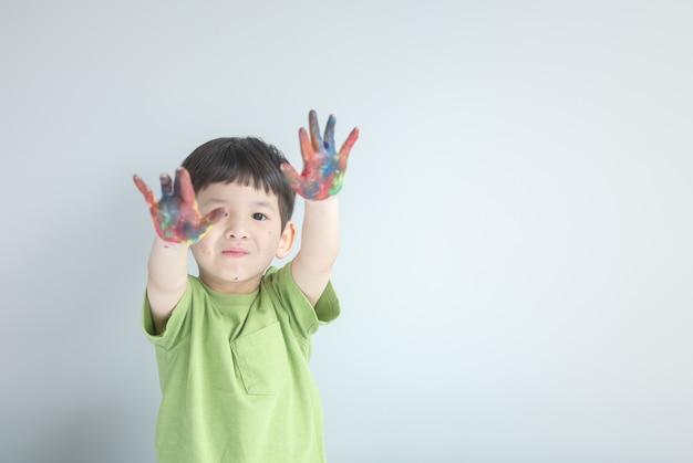 Closeup happy kid show off his colored hands