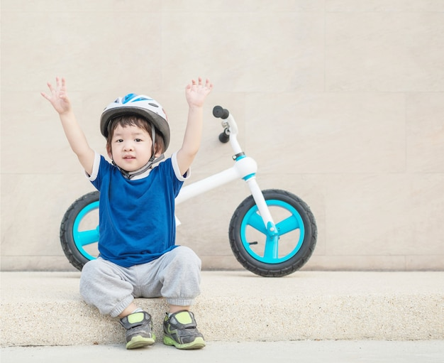 Closeup happy kid sit and hand up with bicycle on stone wall background