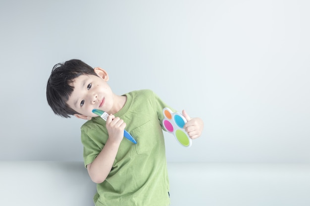 Closeup happy kid with paint brush and palette Premium Photo