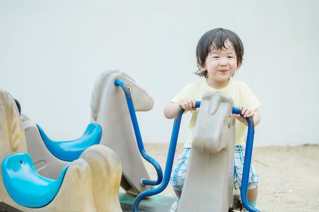 Closeup happy kid with smile face play carousel toy in the playground