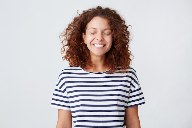 Closeup of happy lovely young woman with curly hair wears striped t shirt