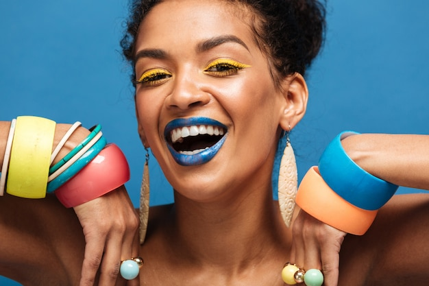 Closeup happy mulatto woman with colorful makeup laughing and showing beautiful adornment on her arms, isolated over blue