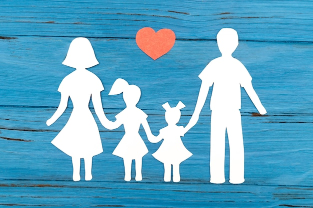 Closeup of happy paper family on blue surface