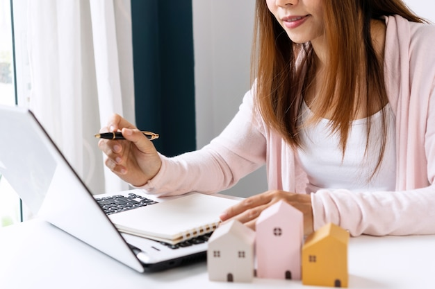 Closeup of happy young asian woman searching home information online