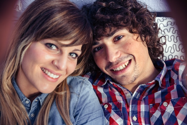 Closeup of happy young couple in love taking a selfie lying over a bed. selective focus on man.