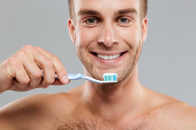 Крупным планом счастливый молодой человек, держащий зубную щетку с зубной пастой