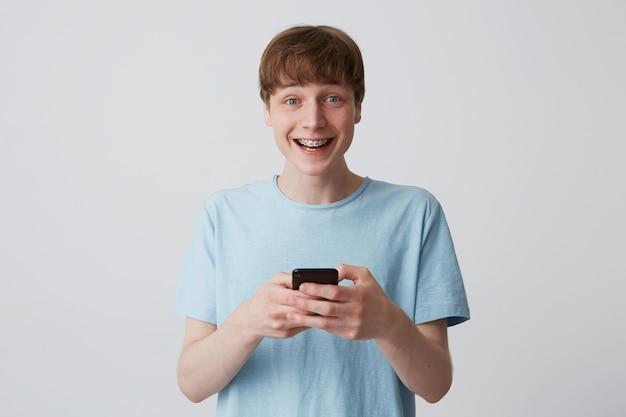 Primo piano di felice giovane studente con breve haicut e parentesi graffe sui denti indossa maglietta blu