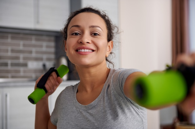Closeup of a happy young woman exercising with dumbbells at home. stay at home concept.