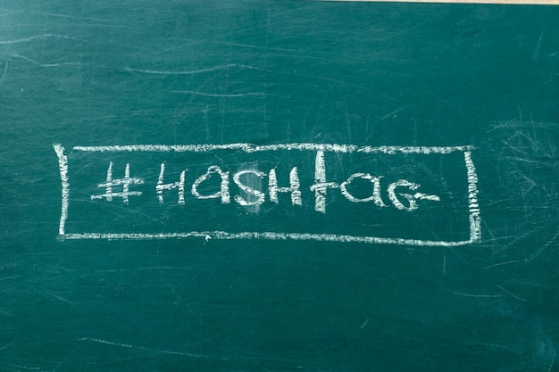 Closeup on hashtag symbol white chalk on a green blackboard copy space