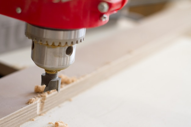 Closeup of the head of the drilling machine with nozzle in the furniture workshop