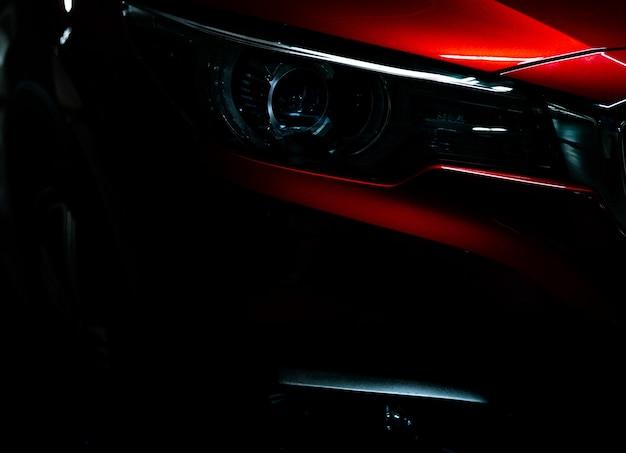 光沢のある赤い高級suvコンパクトカーのクローズアップヘッドライト