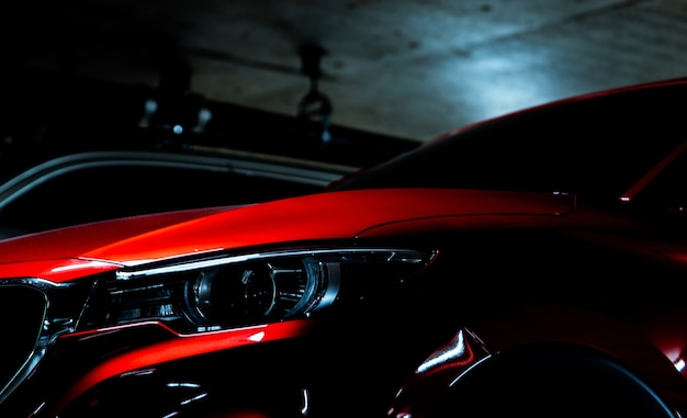 Closeup headlight of shiny red luxury suv car parked in shopping mall underground parking