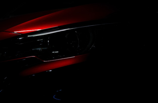 Closeup headlight of shiny red luxury suv compact car. elegant electric car technology