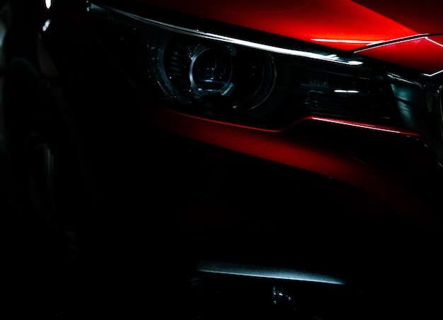 Closeup headlight of shiny red luxury suv compact car