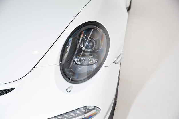 Closeup of the headlight of a white luxury car under the lights against a grey background