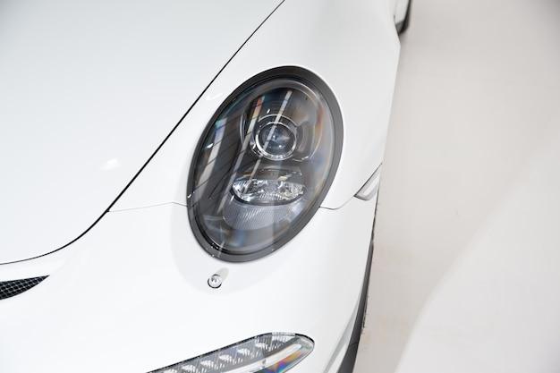 Primo piano del faro di un'auto di lusso bianca sotto le luci su uno sfondo grigio