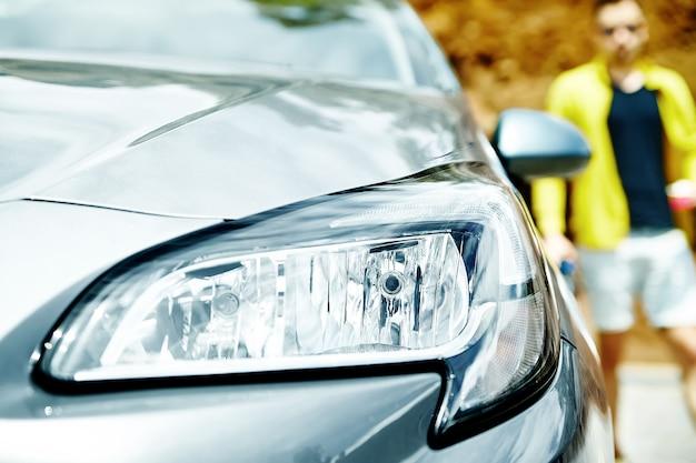 Closeup headlights of gray car with man