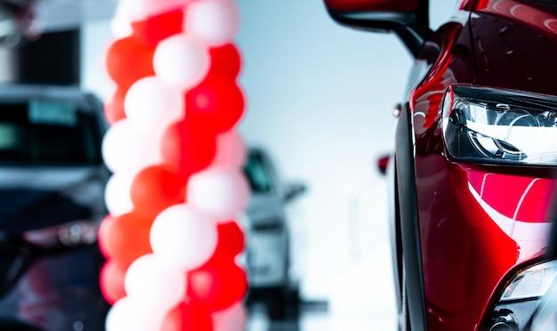 赤いsuv車のヘッドライトをクローズアップ。セールのプロモーションイベントが開催されるモダンなショールームに駐車された新しい高級suv車。自動車販売店。電気自動車事業。自動車リース。自動車産業。