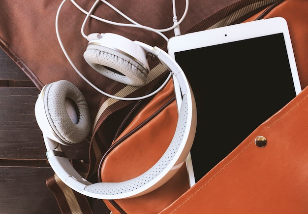 Closeup headphones and tablet computer in bag on wooden table