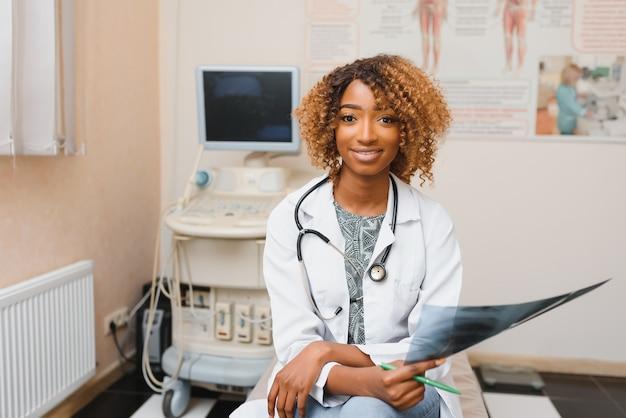 Closeup headshot portrait of friendly, smiling confident female healthcare professional with lab coat