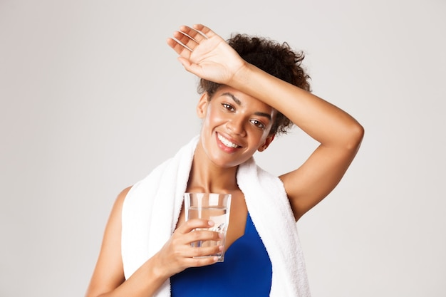 Closeup of healthy beautiful fitness woman with towel wrapped over shoulders wiping sweat off forehe...