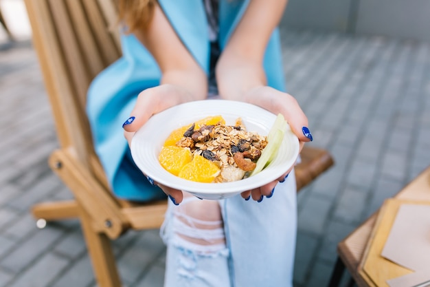 Closeup of healthy breakfast in hands of young woman sitting in chair