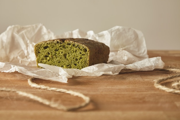木の板に分離されたクラフト紙のスピナッシュ生地からクローズアップ健康ダイエット緑のパン