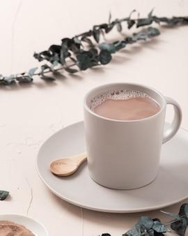 コーヒーカップと白いテーブルの上のいくつかの装飾のクローズアップハイアングルショット