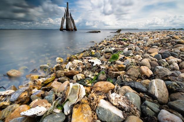 Colpo di alto angolo del primo piano delle pietre su una spiaggia con un mare calmo sul lato sotto un cielo nuvoloso