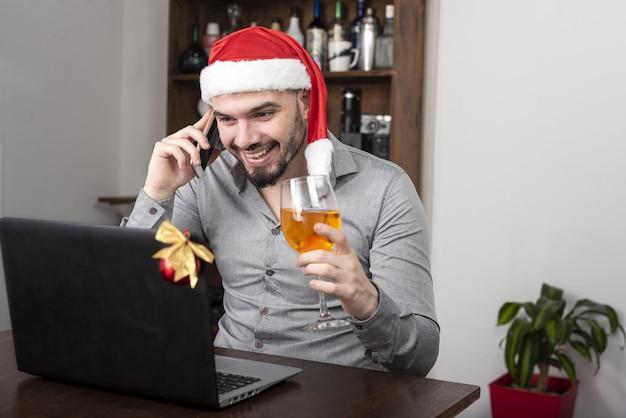 Primo piano di un uomo ispanico che indossa un cappello da babbo natale, gustando il suo vino e parlando al telefono