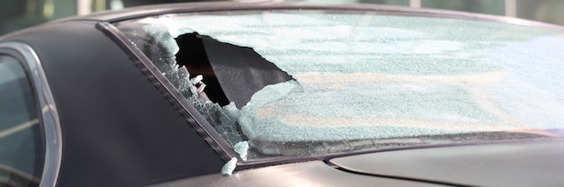 Closeup of hole in rear window of car. stealing things from car concept