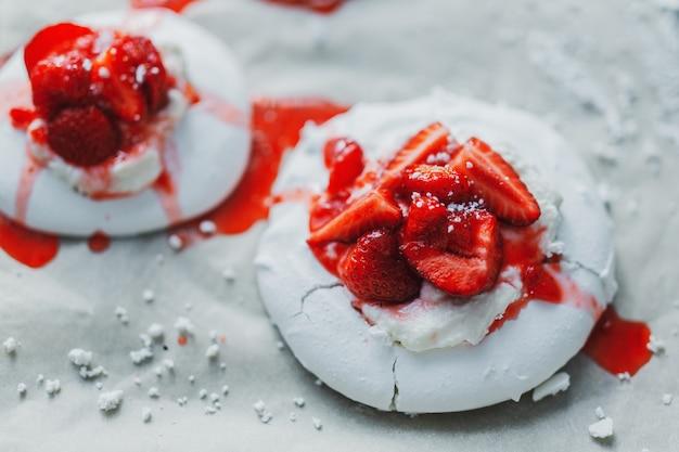 Primo piano di merengue baiser bianco fatto in casa con fragole e marmellata.