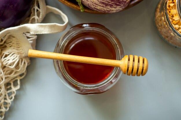 ガラスの瓶にクローズアップの蜂蜜は平らに横たわっていた。有機バイオ製品