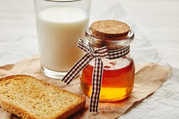 Primo piano del barattolo di miele cucito con nastro adesivo come regalo. bicchiere di latte non focalizzato e pane tostato di segale secco intorno. tutto su carta artigianale.