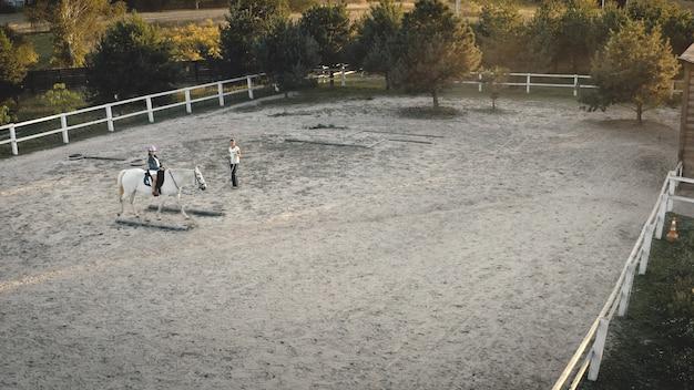 競馬場ビーグルで馬の調教師の散歩に座ってクローズアップ乗馬トレーニング空中トップダウンの女の子