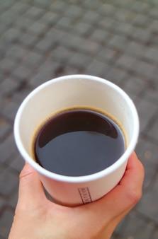 手に持ち帰りの紙コップでクローズアップホットコーヒー