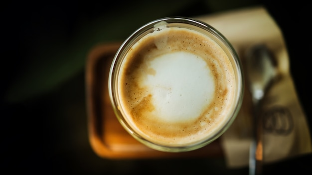 Closeup of hot coffee latte in cup on table. top view. cafe or restaurant scene